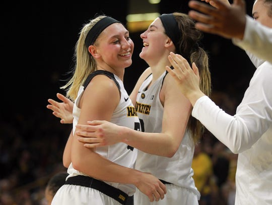 Iowa senior Carly Mohns, left, gets a hug from Megan