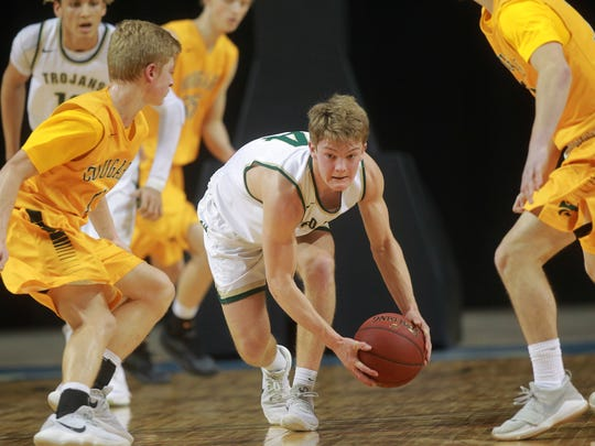 West High's Evan Flitz scoops up a loose ball during the Trojans' game against Cedar Rapids Kennedy at the U.S. Cellular Center in Cedar Rapids on Tuesday, Feb. 27, 2018.