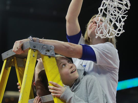 Drake associate head coach Allison Pohlman gets help from her family as she cuts down the nets following the Bulldogs' MVC Tournament championship win against UNI at the TaxSlayer Center in Moline, Ill. on Sunday, March 11, 2018.