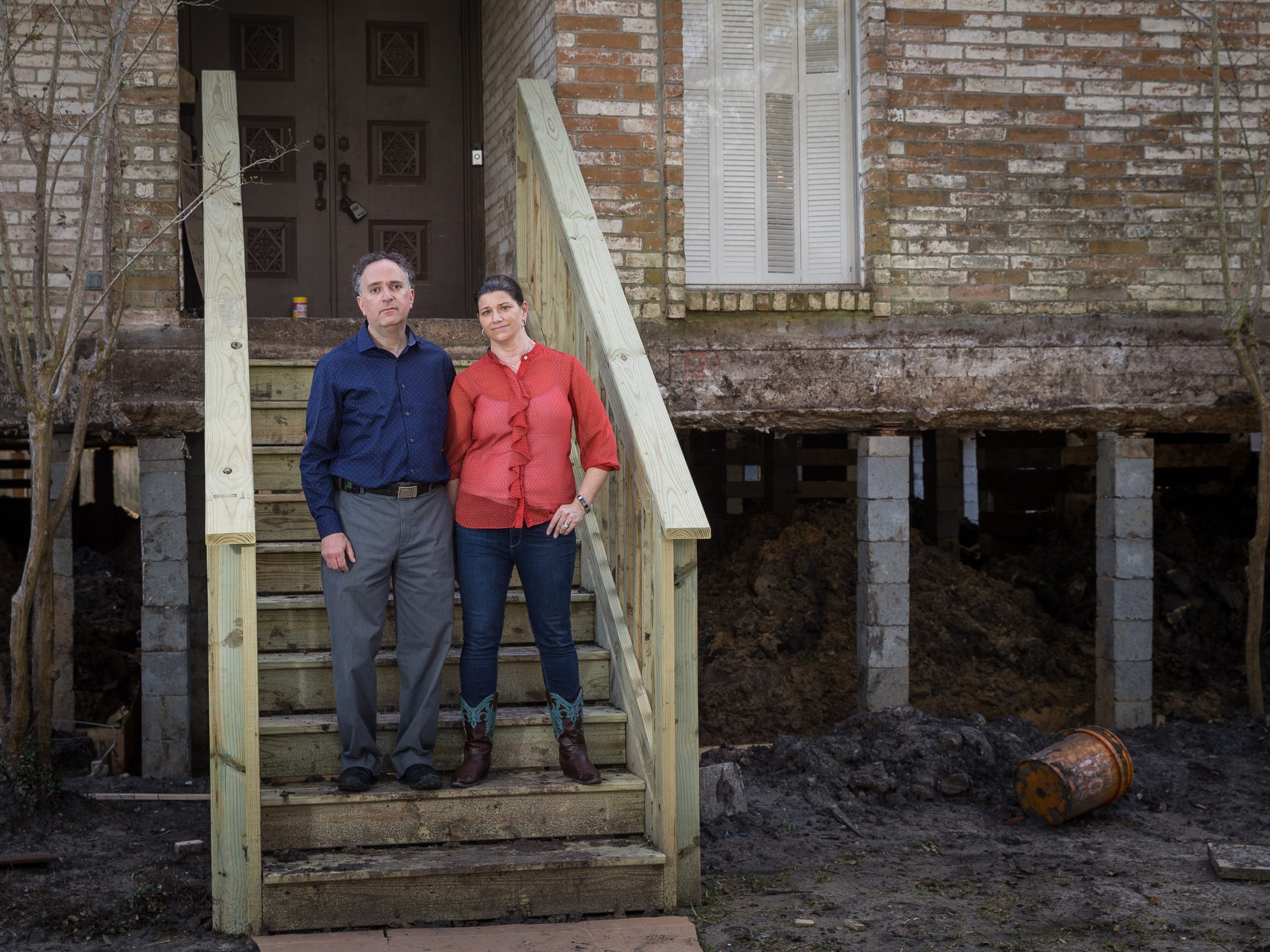 Dave Schwartz and Marni Axelrad, husband and wife, stand for a portrait at their home in Houston on Friday, Feb. 23, 2018. The house is being repaired and elevated due to significant damage from Hurricane Harvey, but Schwartz and Axelrad hope to move back in sometime in March. (Loren Elliott for The Texas Tribune)