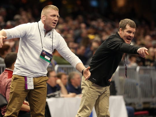 Iowa assistant coach Ryan Morningstar, left, and head coach Tom Brands watch Alex Marinelli wrestle Purdue's Jacob Morrissey at 165 pounds at the NCAA Wrestling Championships at Quicken Loans Arena in Cleveland, Ohio on Thursday, March 15, 2018. Marinelli pinned Morrissey in 6:20.