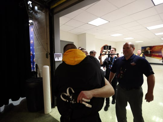 Iowa's Spencer Lee gets a hug from Alex Marinelli after