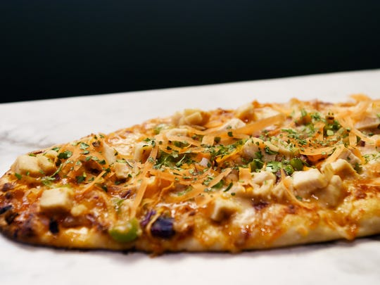 The Casual Pint's Spicy Thai flatbread with chicken, spicy chili sauce, mozzarella cheese, green peppers and red onion garnished with carrots and cilantro.