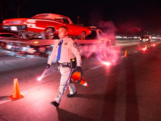 Highway Patrol Officer Benjamin Gomez places flares after a solo crash on the 110 Freeway in Los Angeles, California  on Friday, April 13, 2018.