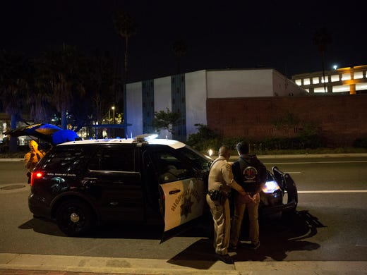 Highway Patrol Officer Benjamin Gomez arrests an unidentified