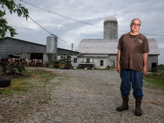 Warren Cheek stands in front of his dairy barn in Cox's Creek.