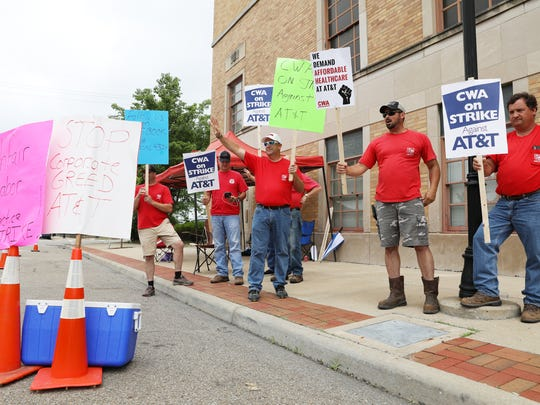 Workers from the Communications Workers of America Local 4324 picket outside of AT&T's facility on Sixth Street in Zanesville on Friday.