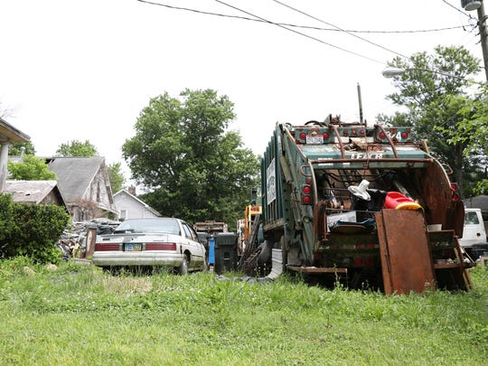Disabled vehicles, including three sanitation trucks, were parked several feet outside Judy Frash's back door in June. Frash's daughter filed a complaint with the health department in May stating the trash was drawing rats to her mother's home.