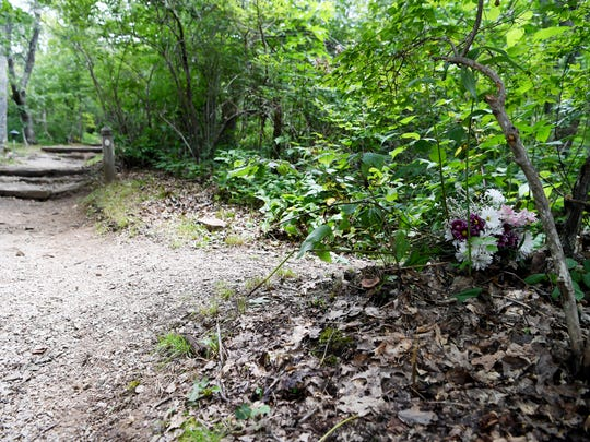 Flowers have been placed at the head of the trail where a Pisgah Inn employee was found dead Tuesday.