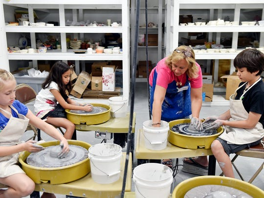 "From left, Aubrey Fetrow, 9, and Adelina Vaida, 8, work to shape their clay to make vessels as instructor Allison Seitz assists Victor Vaida, 10, during Creative York's Clay Camp summer program Thursday in York. Creative York is hosting more than a dozen week-long ""arts discovery camps,"" ranging from creative writing to fiber art to theater."