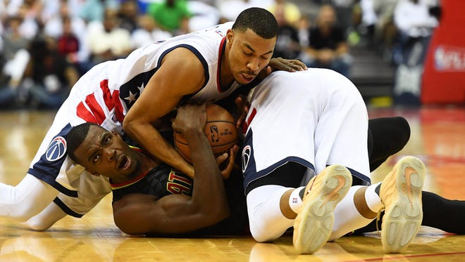 Atlanta Hawks forward Paul Millsap (4) and Washington Wizards forward Markieff Morris (right) and forward Otto Porter Jr. (left) fight for a loose ball during the second quarter in game one of the first round of the 2017 NBA Playoffs at Verizon Center.