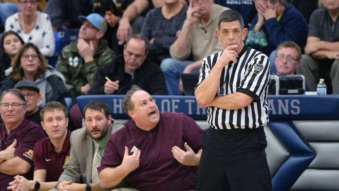 Kennedy Catholic High School head basketball coach Rick Mancino, center, questions a call with official L.J. Frisina during a Region 7 basketball game in Millcreek Township on Jan. 24, 2020. Mancino resigned Thursday after 11 seasons as Golden Eagles head coach.
