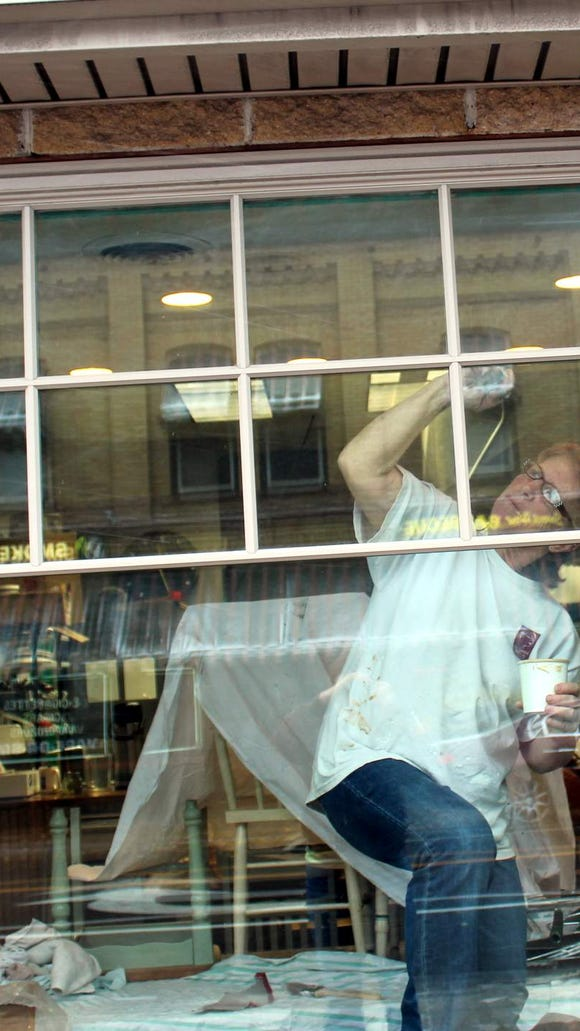 Marie Hickey paints the trim on Barry's front window. (M. Rosenberry)
