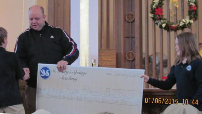 Students at St. Mary's Springs Academy raised $2,732 and donated it to Leila Hope Adamson. The students conducted several fundraisers and presented the check to Leila's father, James Adamson, back left, at their Epiphany service. SMSA fourth grade students Sam Coon is at front left, with Tori Fabricius, at right.