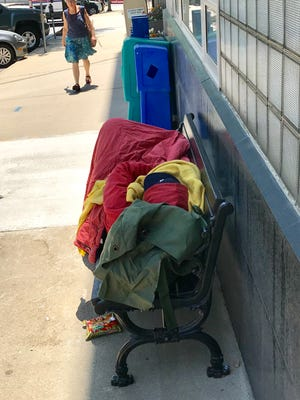 The city of Asheville does not allow camping on public property. This homeless person was sleeping under camping gear downtown on Friday.