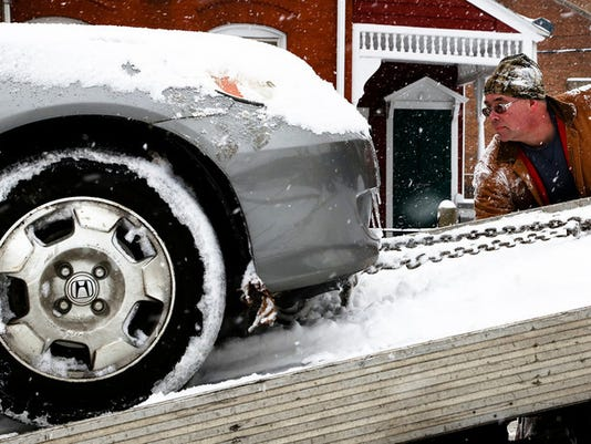 Mike Darrah, owner of Darrah's Automotive and Recycling tows one of the last cars on S. Queen St. in York, Tuesday. (Sonya Paclob - Daily Record / Sunday News)