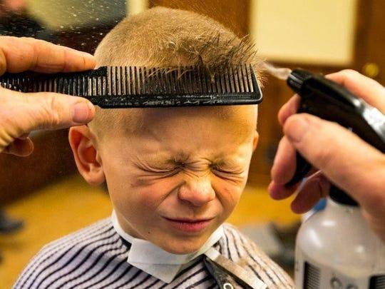 Don Vruggink gives his grandson, Hessel Vruggink, 6, a haircut at Don's Barber Shop in Hudsonville.