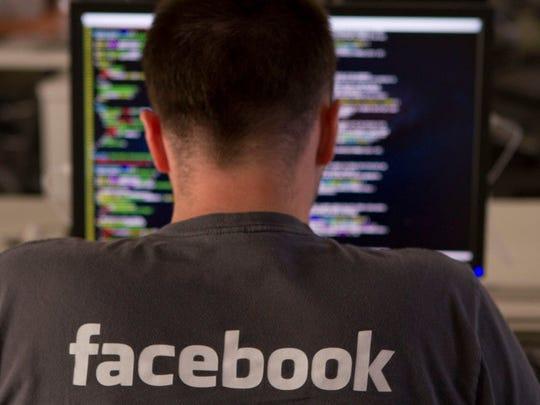 A Facebook employee entering computer code on his laptop.