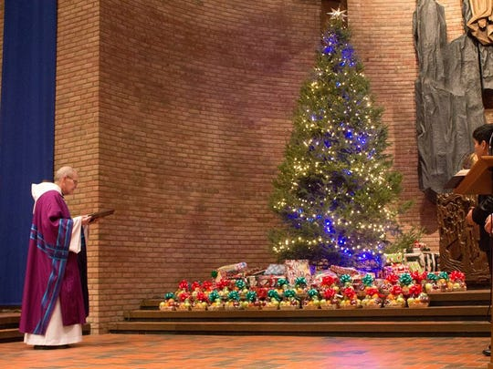 Rector John Holly of St. Lawrence Seminary High School prays over gifts that students would later deliver to children of incarcerated families across the region.