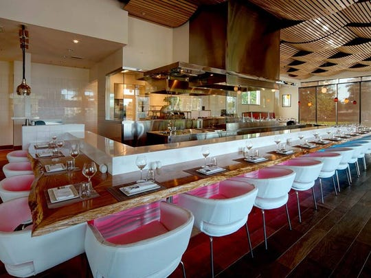 U-shaped chairs wrapped in buttery leather surround the glass-encased kitchen at Lamoraga in Naples.