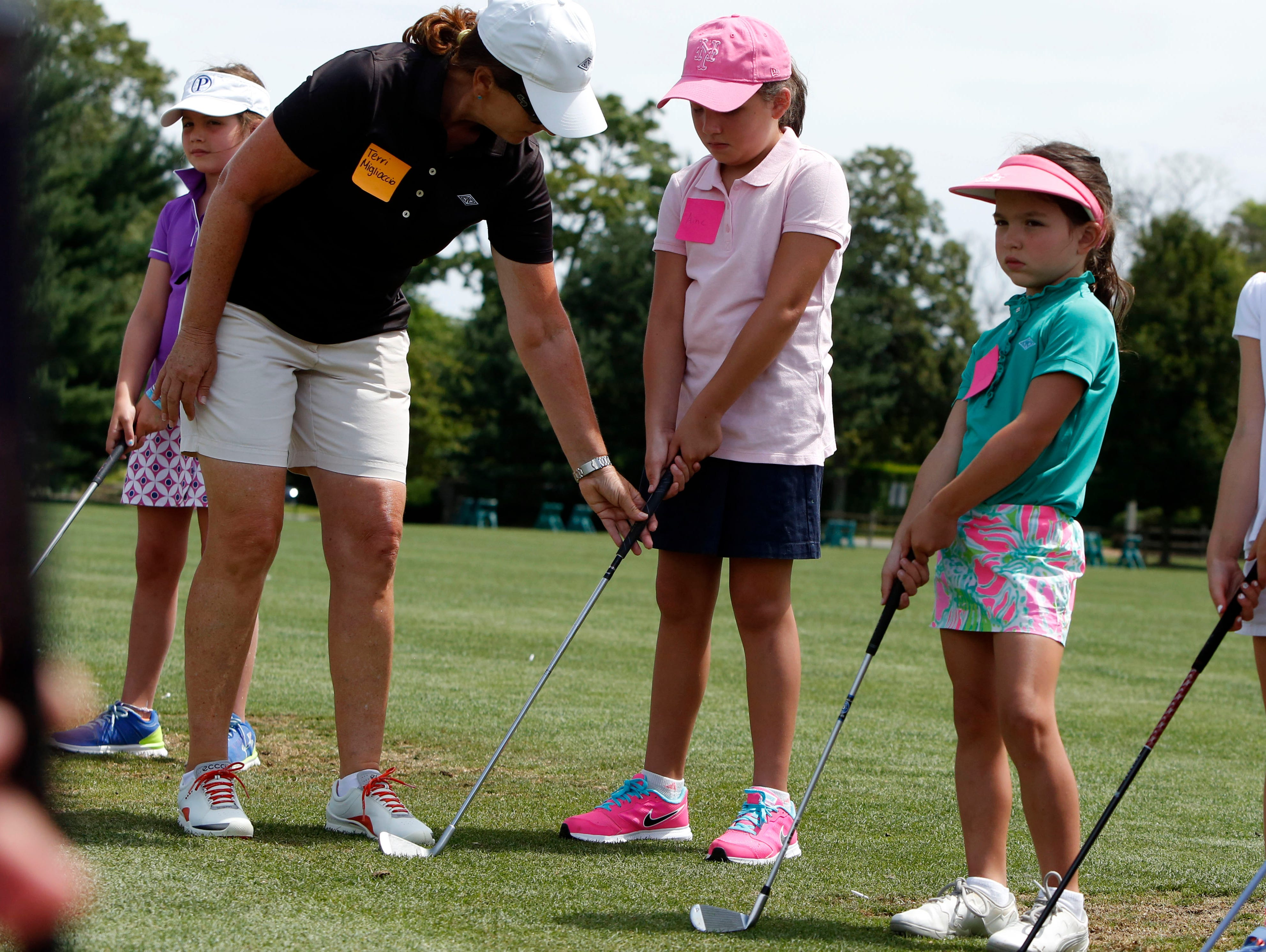 Golf professional Terri Migliaccio guides Aine Breen, 8, of Port Chester during the annual Girls to the Tee event put on by the Women's Metropolitan Golf Association at Westchester Country Club in Rye, Aug. 8, 2016. The free clinic, for girls ages 6-18, is an afternoon of instruction and networking to help show girls who are learning the game that they are part of a larger group.