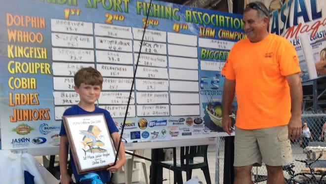 Logan Rapp, left, took top junior angler honors for a 23.8-pound kingfish, as tournament weighmaster, Capt. Doug Kaska looks on.