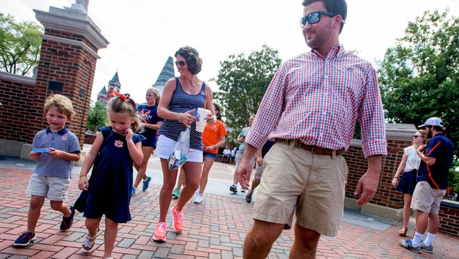 The Karcher family, Russell and Rebecca and their children Katie and Jake, walks at Toomer's Corner before the Auburn Clemson game in Auburn, Ala., on Saturday September 3, 2016.