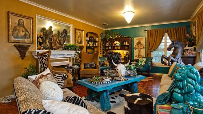 Photo by Eddie Seal/Special to the Caller Times The living area is alive with color and art, featuring a turquoise coffee table made by the homeowner from an antique door.  Religious and all types of art mix well with animal print furniture and western artifacts and statuary.