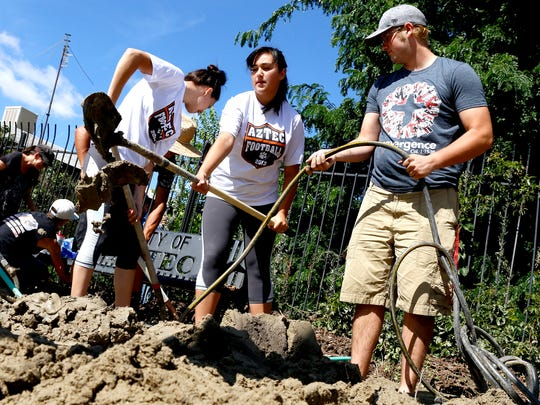 Jiovona Sandoval, left, Zoe Selph, and Brian Umbarger, all of Aztec, move dirt and debris to a pile Aug. 27 as part of a cleanup effort at the Aztec Museum.