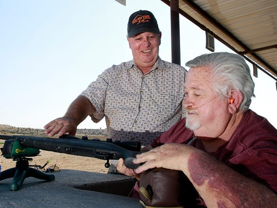 "Carey ""Kirt"" Stidman, right, and Craig Hunter talk after Stidman fired his rifle for the first time on June 21 at the San Juan Wildlife Federation shooting range in Farmington. Hunter has launched a new program to teach people with disabilities how to shoot guns."