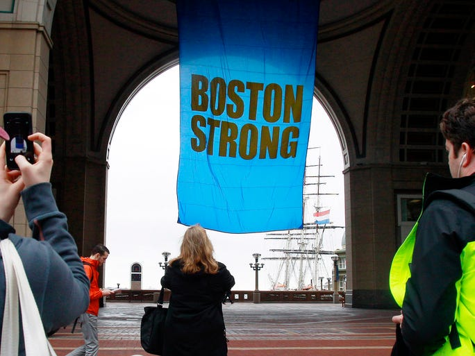 People photograph a banner at Rowes Wharf on the first anniversary of the Boston Marathon bombings on April 15 in Boston. Three people were killed and 260-plus injured in last year's explosions near the finish line of the race.