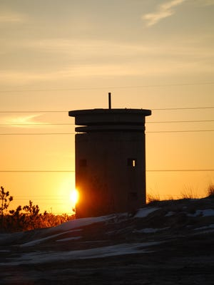 The sun sets behind an old World War II tower just south of South Bethany.
