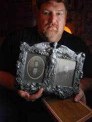 Chris Troy holds photos and cigar box he found in a closed-off fireplace in a Port Huron home. He believes the photos are of a woman named Catherine Dodge.
