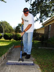 Volunteers clean sidewalks during the Day of Caring
