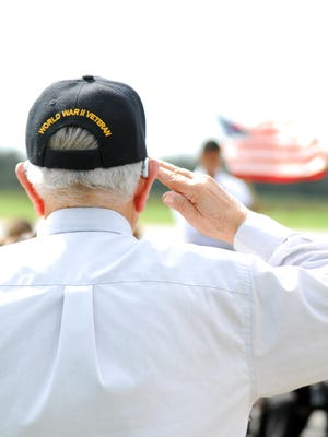A WWII Veteran salutes the American flag as the Star Spangled Banner plays at a Veterans Day celebration in Eunice.