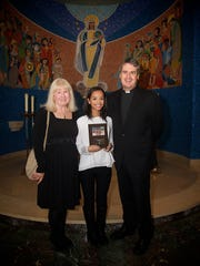 Alyssa Sierra with her art teacher,  Rose Lavin Pennyfeather, and the Rev. Andrew Small.