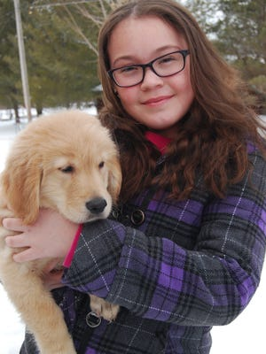 Brookelynn Fleming holds Riley, a golden retriever puppy. Brookelynn  is a Leap Year baby and celebrates her third birthday Feb. 29.