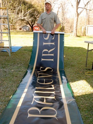 Tony Davoren, co-director of the Celtic Bayou Festival rolls up the banner for the Irish Pub facade.