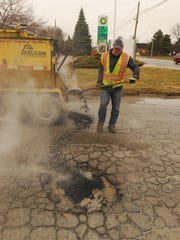 St. Clair County Road Commission employee Jim Blake fills a pothole off 24th Street in Port Huron Township.