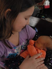 Kaylin Bird holds her new baby sister, Addalyn Johnson. Kaylin and her great-grandmother, Janice Paling, helped deliver Addalyn when mom, Erica Paling, went into labor March 26.