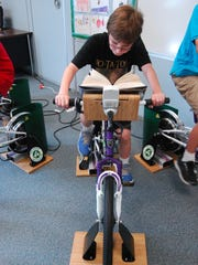 Fifth-grader Marc Thompson reads and rides at Avoca Elementary School.