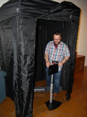 Chris Ashwell with the Street Stories project sets up a recording device in a story booth at the Price Hill Story Gallery. Visitors to the gallery will be able to record personal stories that will then be shared with others,