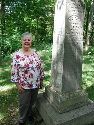 Peg Schmidt with the Delhi Historical Society stands Sept. 15, 2017, next to the grave of Henry Darby, who was rumored to have been involved with the Underground Railroad. Darby's grave will be among those featured during a cemetery tour Oct. 21.