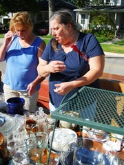 Sisters Julie Klieman, left, and Debbie Schweihofer look for bargains at the white elephant sale during St. Mary's Fall Festival in St. Clair.