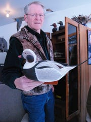 Bud Shell, of East China Township, holds a decoy he carved of a long-tailed duck.
