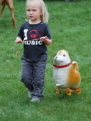 A young participant and her balloon dog set out to walk the course at the Dutchess Day School's dog walk.