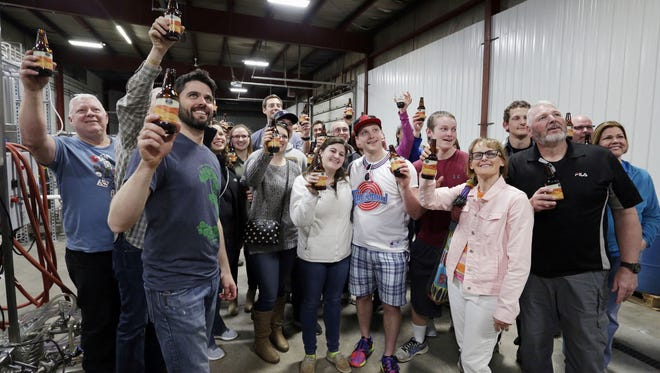 People taking the tour at 3 Sheeps Brewery during the company's 5th year celebration, raise their glasses for a company photographer Saturday April 8, 2017 in Sheboygan.
