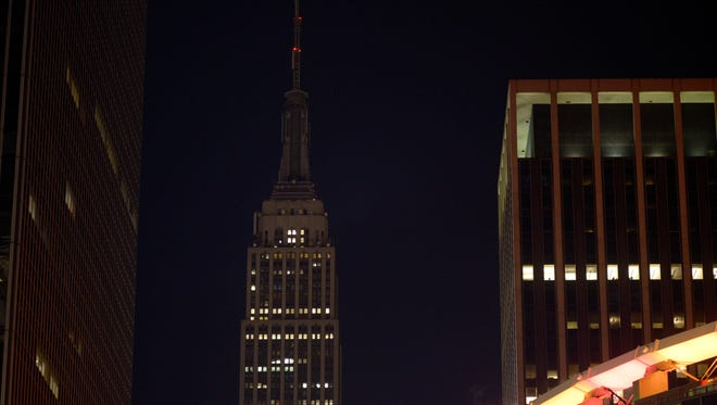 In this Nov. 14, 2015, file photo, the Empire State Building in New York went dark for a second night in sympathy for people of Paris.