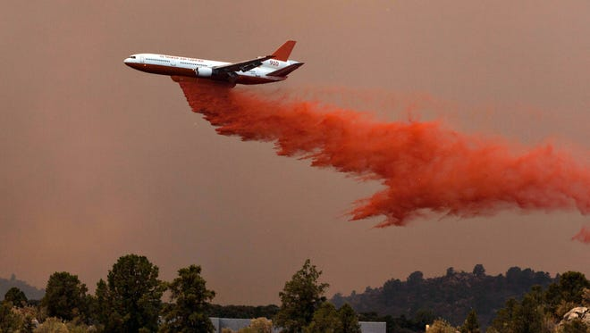 A former Arizona hotshot superintendent is suing the federal government to obtain aircraft radio transmissions that may help explain the deaths of 19 firefighters in 2013's Yarnell Hill Fire. Here, a low-flying slurry bomber drops retardant near Peeples Valley during the blaze.  Tom Story/Special for the Republic