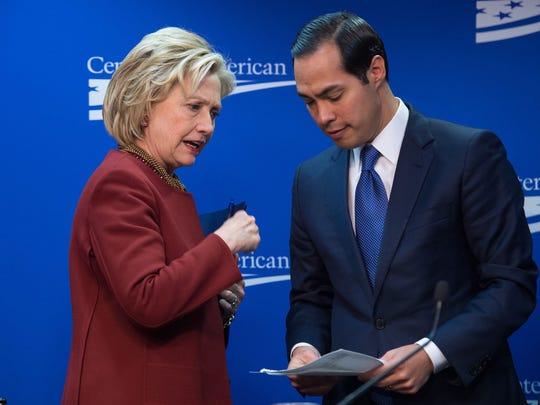 Hillary Clinton talks with Julian Castro after taking